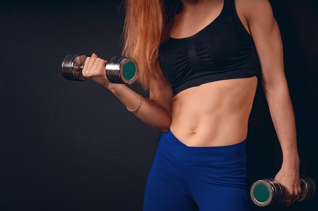 女の子の運動はダンベルを持ち上げます。ダンベルで上腕二頭筋の運動。フリーテキストスペース。