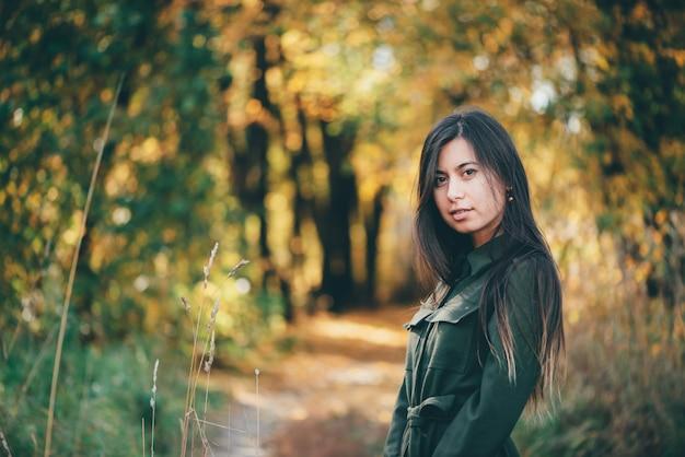 Girl on autumn bokeh background in sunset.