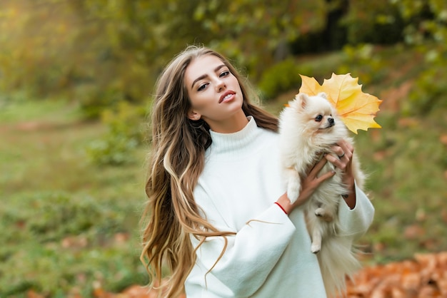 Girl in autumn. emotional support with pets. woman with doggy on fall maple leaf outdoors.