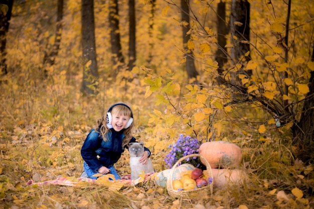 Girl in the autumn forest. with a kitten