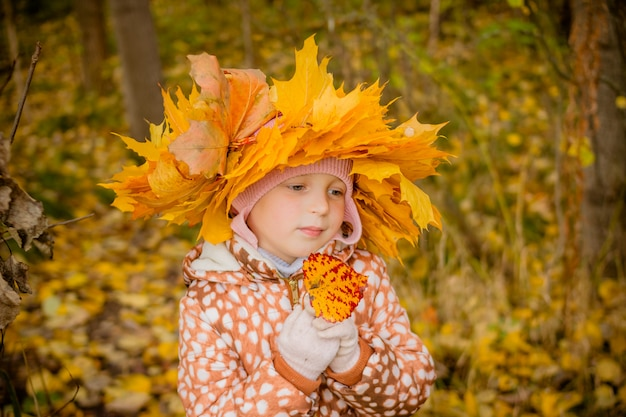 Girl in autumn golden park with a wreath of leaves.