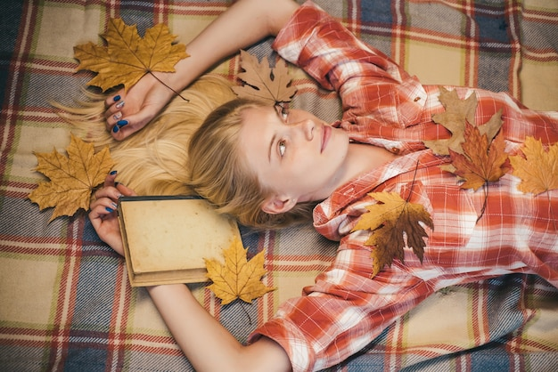 Girl in autumn in a seasonal clothes whith golden leaf. beautiful sensual blonde playing with leaves. sensual woman wearing pullover and looking at camera. fashion portrait of beautiful sensual woman.