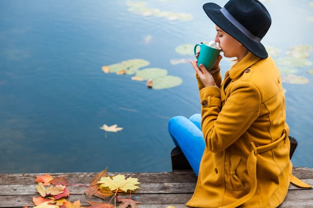 Girl in the autumn the water heats about a cup of hot tea