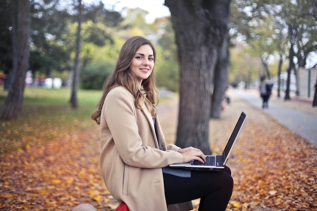 Girl in autumn with a laptop in a park