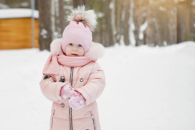 Младенец девочка в розовом комбинезоне в кепке с помпоном идет по белому снегу.