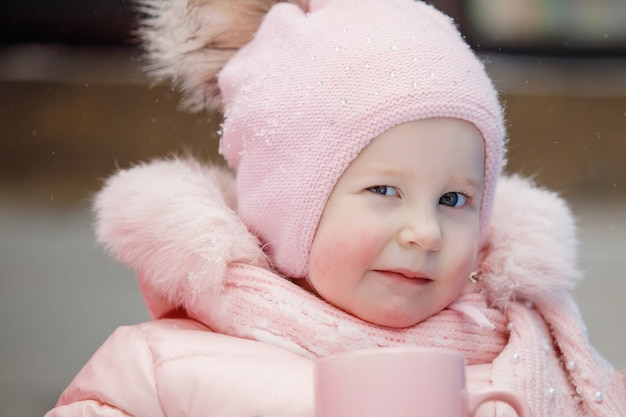 Девочка-младенец в розовом комбинезоне в кепке с помпоном лукаво подмигивает. солнечный зимний день в городском парке, на открытом воздухе.