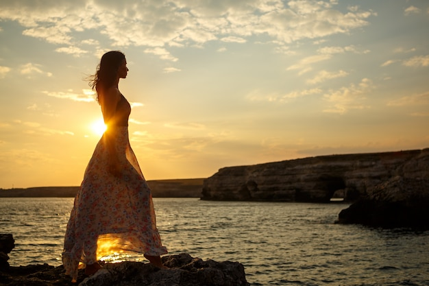 The girl on the background of a beautiful seascape and sunset, silhouette of a girl on a cliff, on a cliff, beautiful sky and sea