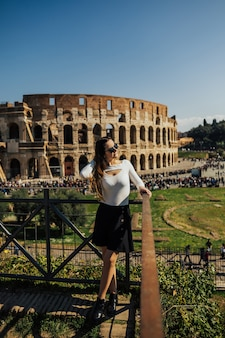 Girl on the background of the majestic ancient colosseum in rome.