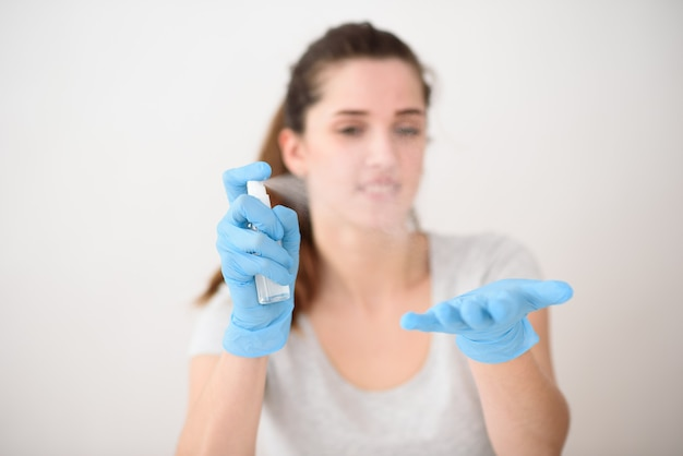 The girl in the background sprays antiseptic on the palms of her hands in rubber gloves.