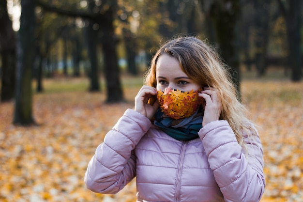 The girl on the background of trees in the park puts on a mask with autumn leaves