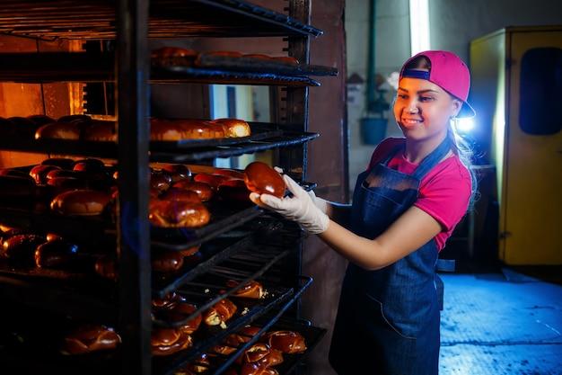 パン屋に立っている間、彼女の手で新鮮なパイを持っている女の子のパン屋。彼女はデニムのエプロンとキャップを着ています。ベーカリー製品の製造。ホットクリスピーペストリーの棚。
