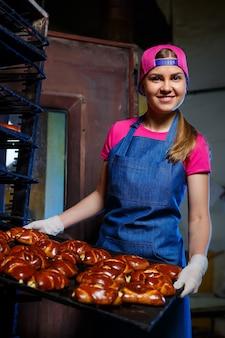 女の子のパン屋は、パン屋で熱いペストリーが入ったトレイを持っています。ベーカリー製品の製造。新鮮なサクサクのペストリーラック