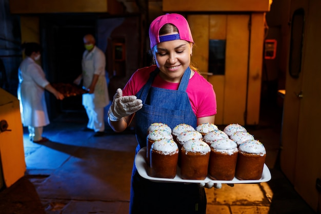 Девушка-пекарь держит поднос с горячей выпечкой в пекарне. на ней джинсовое платье и кепка. производство хлебобулочных изделий. полка со свежей хрустящей выпечкой.