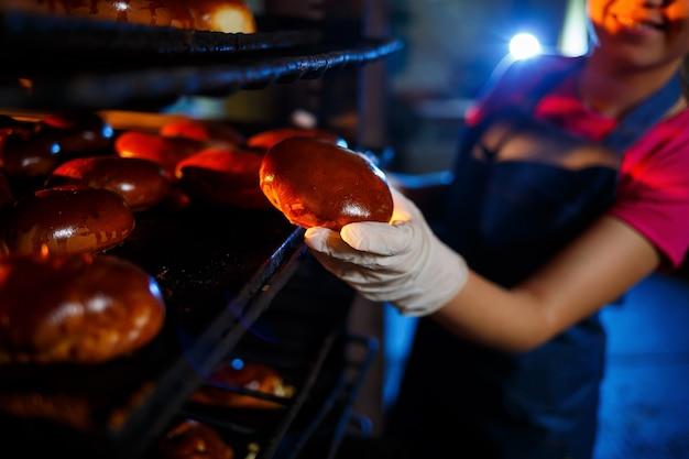 女の子のパン屋は、パン屋の手に新鮮なパイを持っています。彼女はデニムのフロックとキャップを着ています。ベーカリー製品の製造。ホットクリスピーペストリーをラックに入れます。