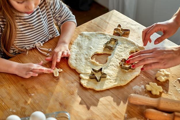 어머니와 함께 쿠키를 굽는 소녀, 쿠키 절단을 만들기 위해 금형을 사용하여 반죽을 롤아웃하는 데 도움
