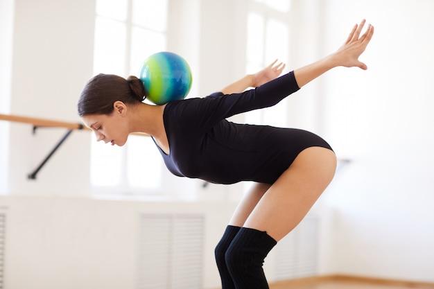 Девушка балансирует мяч на спине