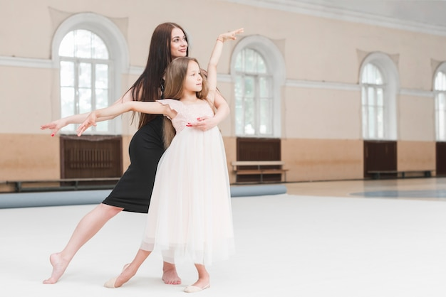 Girl and ballerina teacher dancing together in dance studio