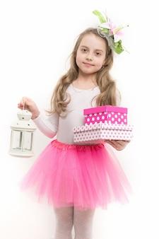 ピンクのスカートのチュチュで長いブロンドの髪に花を持つ少女バレリーナは、白で隔離のランタンとボックスを保持します。クリスマス、新年、休日、誕生日、記念日のお祝い。ボクシングデーのコンセプト