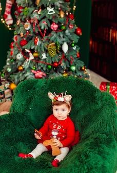 Girl in bambi ears lies on fluffy green carpet