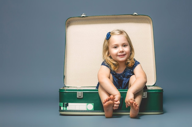 Girl barefoot sitting inside an old suitcase.