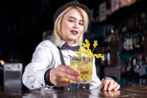 Girl barman makes a cocktail on the alehouse