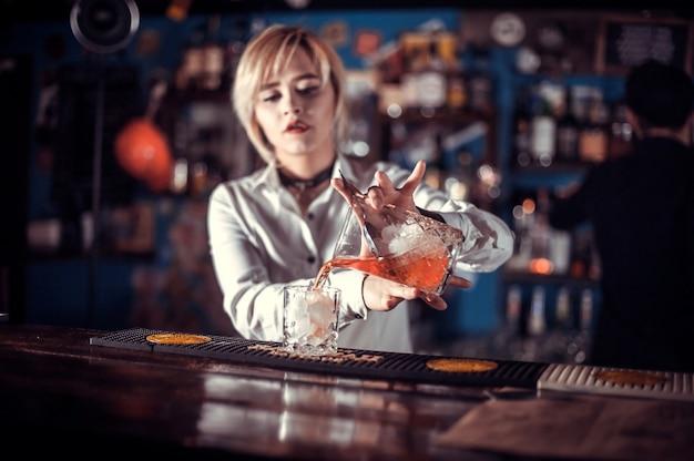 女の子のバーテンダーがバーの後ろでカクテルを混ぜる