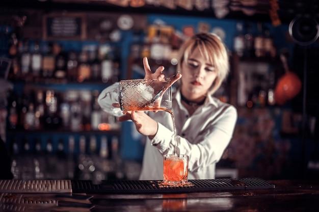 Девушка-бармен придумывает коктейль в баре