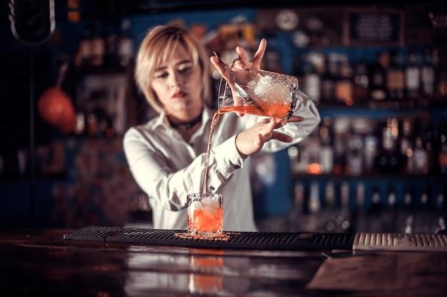 Девушка-бармен готовит коктейль в баре