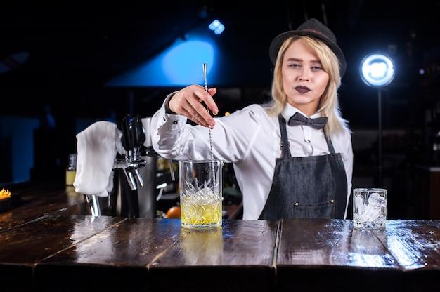 女の子のバーテンダーがブラッセリーでカクテルを作る