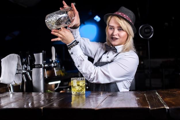 Девушка-бармен создает коктейль в пивном ресторане