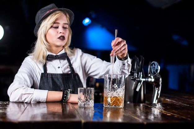 Девушка-бармен делает коктейль в портье