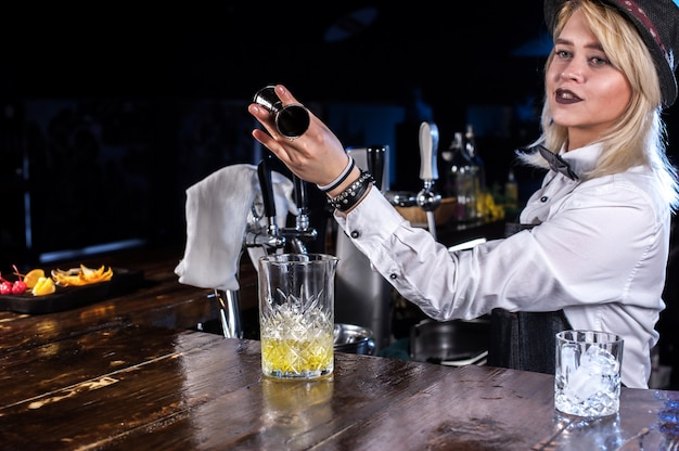 Girl bartender makes a cocktail at the pothouse