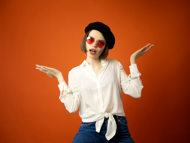 Girl in basque beret, red glasses and white blouse on orange background