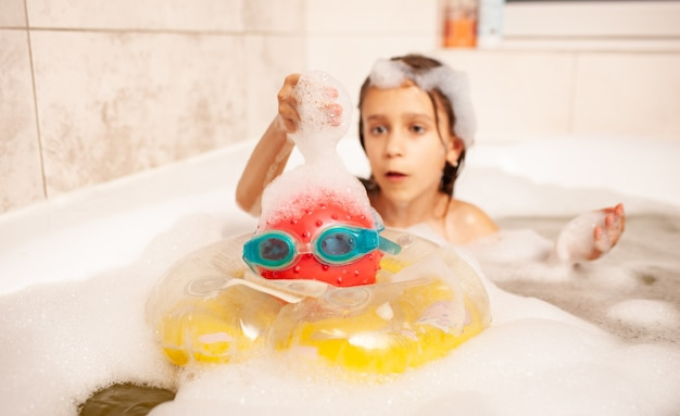 Girl bathes in a bath with foam and plays life-saving ball and swimming goggles
