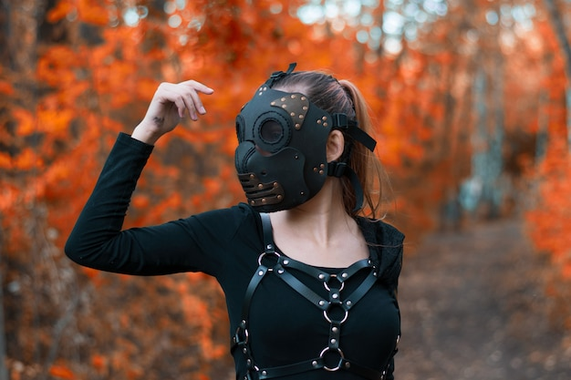 A girl in a bdsm costume and a black mask in a red forest.an idea for halloween.