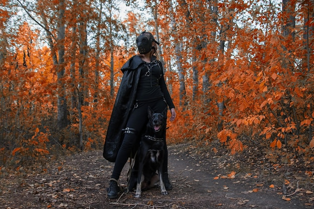 A girl in a bdsm costume and a black mask and with a dog in red forest.an an idea for halloween.