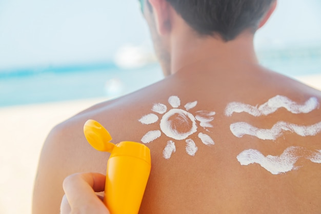 The girl on the beach applies sunscreen to the skin of a man