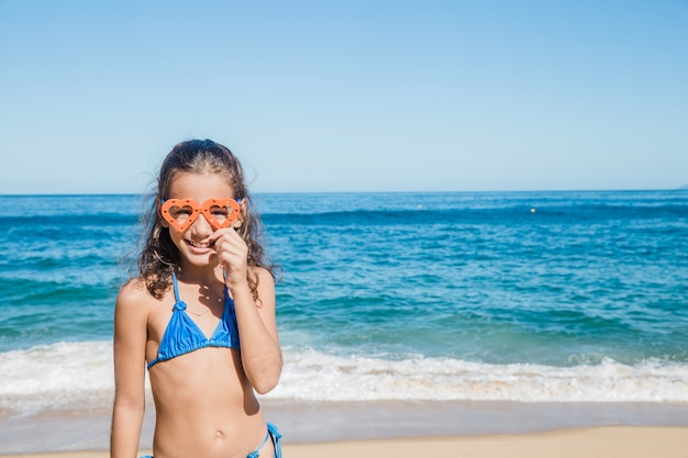 Girl on the beach happy with her goggles
