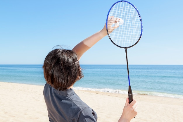 The girl on the beach serves playing badminton. close-up.