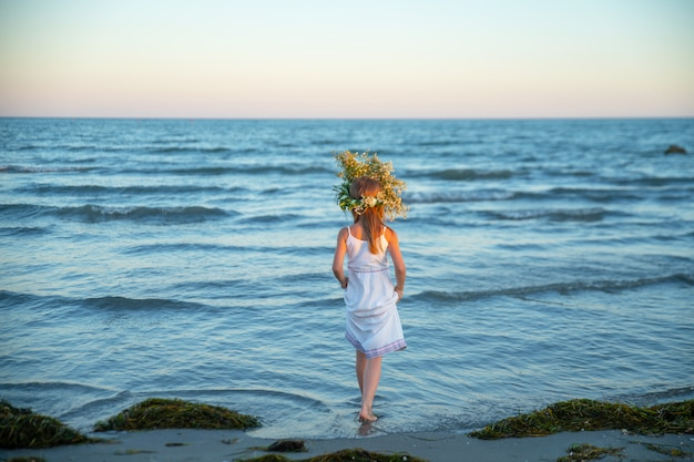 Girl on the beach in a white sundress and with a wreath of wildflowers enters sea water