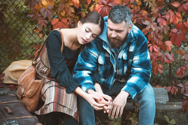 Girl and bearded guy or happy lovers on a date hold hands. dating and autumn love concept. couple in