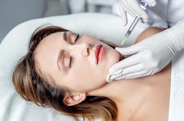 Девушка-косметолог делает уколы на губах и лице красивой женщины в косметической клин. концепция косметологии.