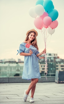 The girl in a beautiful dress holds balloons.
