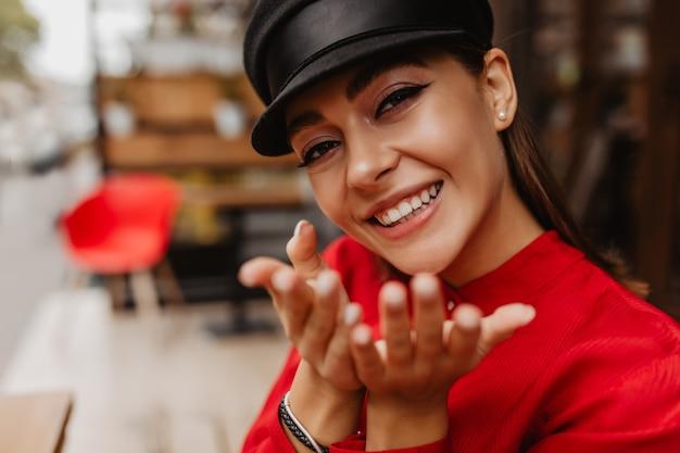 Ragazza occhi marroni splendidamente dipinti con eyeliner, evidenziando le caratteristiche del viso. la modella in camicetta rossa manda un bacio d'aria