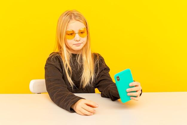 女の子の美容ブロガー。カメラでポーズをとってvlogを作る金髪のティーン。