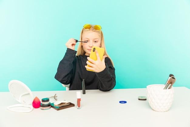 소녀 뷰티 블로거는 블루 스튜디오에 고립 된 동영상 블로그를 만듭니다.
