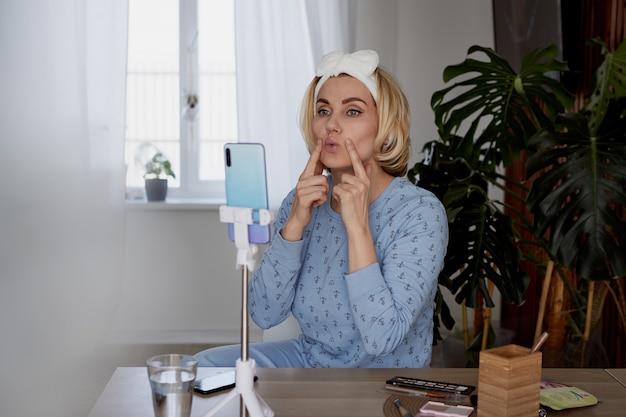 女の子の美容ブロガーは、メイクアップブログ、放送、化粧品のコンセプトについて購読者向けのポッドキャストを記録します