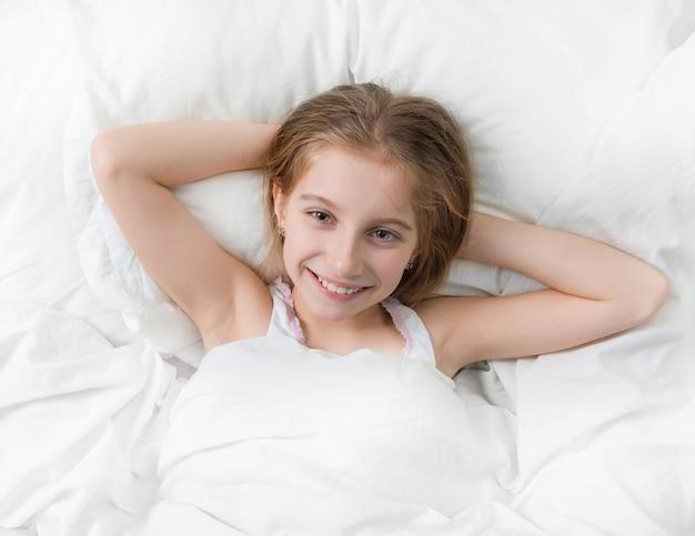 Girl in bed wide awake, hands under head