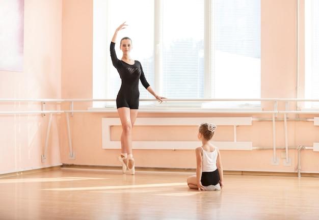 Girl beginner watching classmate standing en pointe in ballet dancing class