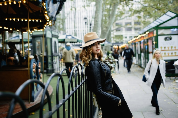 Girl in beige hat leans to steel fence on the street